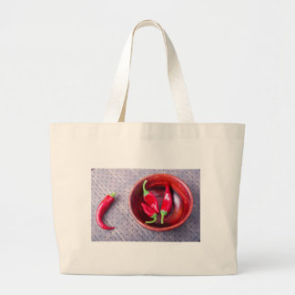 Chilli hot red pepper in a brown wooden bowl large tote bag