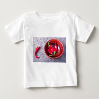 Chilli hot red pepper in a brown wooden bowl shirts