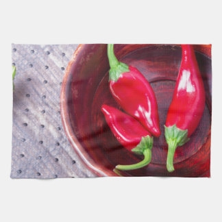 Chilli hot red pepper in a brown wooden bowl tea towel