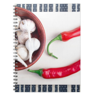 Chilli peppers and garlic in a wooden bowl notebook