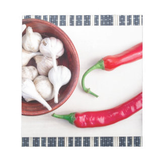 Chilli peppers and garlic in a wooden bowl notepad