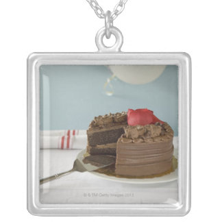 Chocolate cake with missing slice on table, personalized necklace
