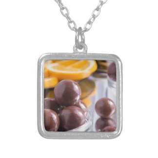Chocolate candies in a small glass bowl close-up silver plated necklace