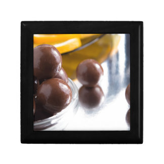Chocolate candies in a small glass bowl close-up small square gift box