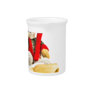 Christmas bear in wooden sleigh on white pitcher