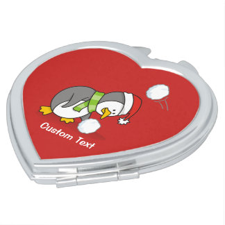 Christmas penguin getting a snow ball compact mirror