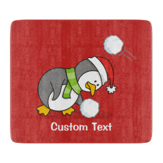 Christmas penguin getting a snow ball cutting board