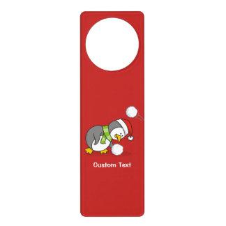 Christmas penguin getting a snow ball door hanger