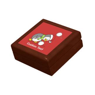 Christmas penguin getting a snow ball gift box