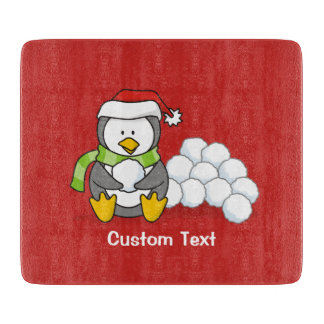 Christmas penguin sitting with snow balls cutting board