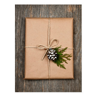 Christmas present in brown paper tied with string postcard