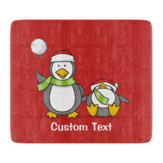Christmas Snowballing penguins Cutting Board