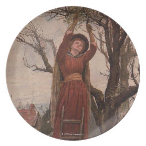 Circa 1820: A young woman cuts mistletoe Plates