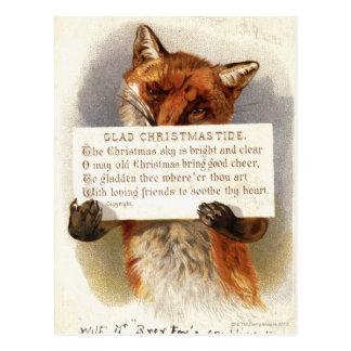 Circa 1900: A fox holds a Christmas verse Postcard