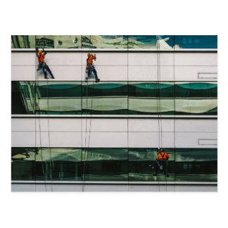 Cleaning windows of a skyscraper postcard