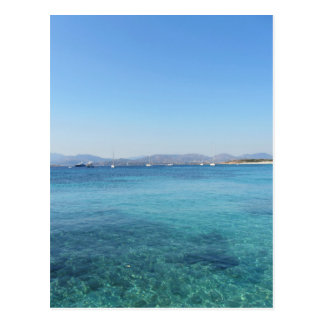 Clear turquoise sea water and boats on the horizon postcard
