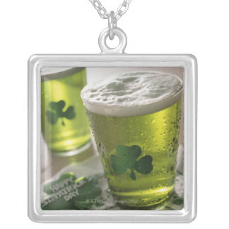 Close up of beverages with shamrocks on glass silver plated necklace