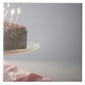 Close up of chocolate birthday cake with candles tile