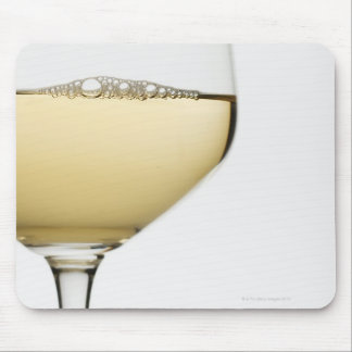 Close up of glass of white wine on white mouse pad