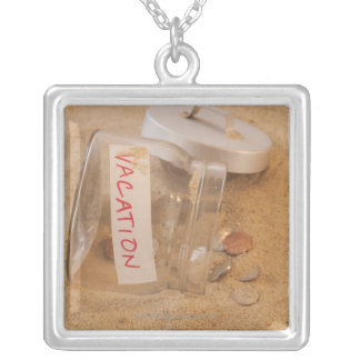 Close up of jar with coins spilled on sand silver plated necklace
