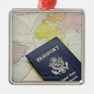 Close-up of passport lying on map metal ornament