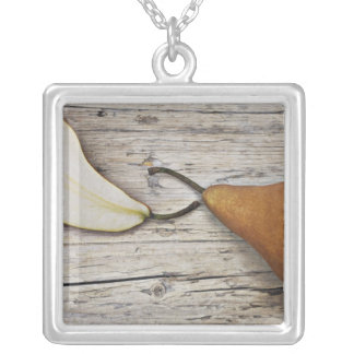 Close up of pear and pear slice on wooden board square pendant necklace