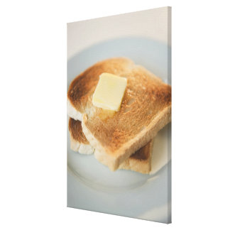 Close up of toasts with butter on plate canvas print