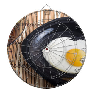 Close-up top view on a black plate with fried egg dart board