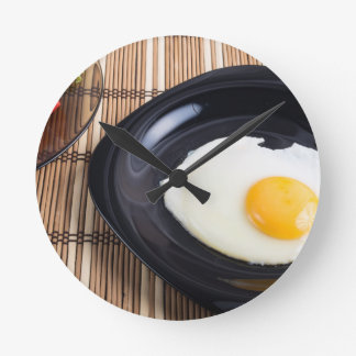 Close-up top view on a black plate with fried egg round clock