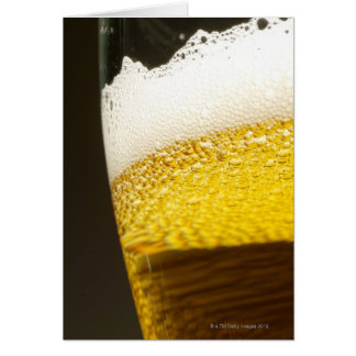 Close up view of beer, bubbles and foam in a card