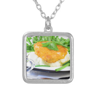 Close-up view of fried chicken silver plated necklace
