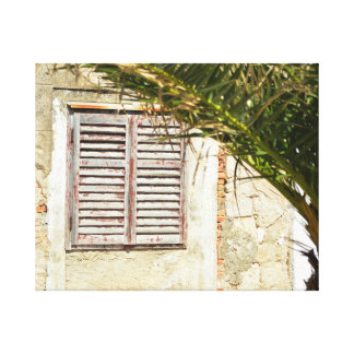 Closed wooden window in an house with palmtree canvas print