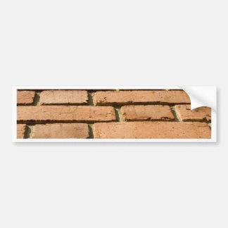 Closeup of a brick wall bumper sticker