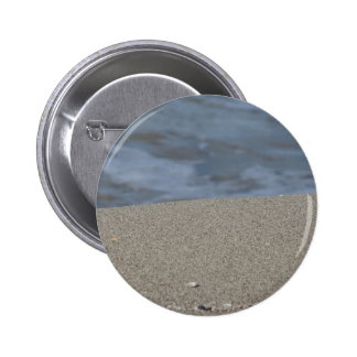 Closeup of sand beach with sea blurred background 6 cm round badge