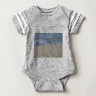 Closeup of sand beach with sea blurred background baby bodysuit