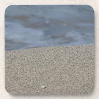 Closeup of sand beach with sea blurred background coaster