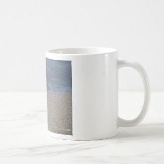 Closeup of sand beach with sea blurred background coffee mug