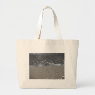 Closeup of sand beach with sea blurred background large tote bag