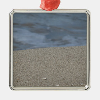Closeup of sand beach with sea blurred background metal ornament