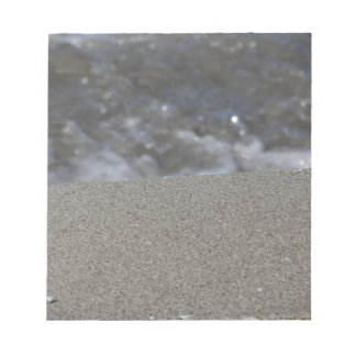 Closeup of sand beach with sea blurred background notepad