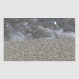 Closeup of sand beach with sea blurred background rectangular sticker