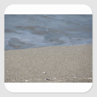 Closeup of sand beach with sea blurred background square sticker