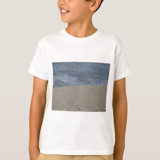 Closeup of sand beach with sea blurred background T-Shirt