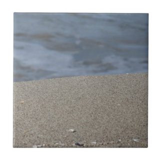 Closeup of sand beach with sea blurred background tile