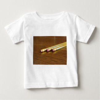 Closeup of used pencil erasers on wooden table baby T-Shirt