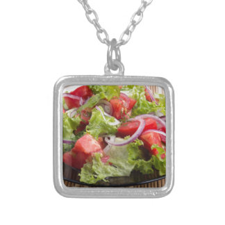 Closeup plate with a salad of chopped tomato slice silver plated necklace