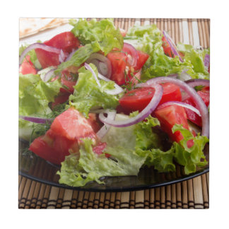 Closeup plate with a salad of chopped tomato slice small square tile