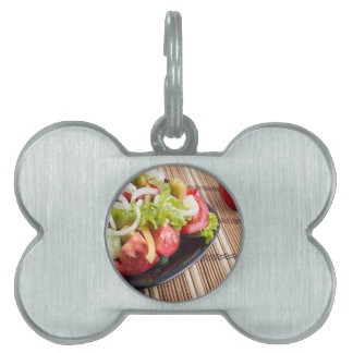 Closeup view fresh natural salad with raw tomato pet tag