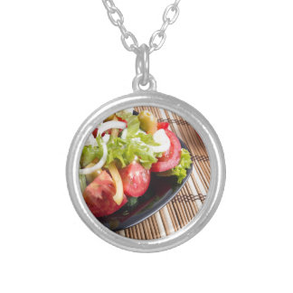 Closeup view fresh natural salad with raw tomato silver plated necklace