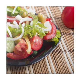 Closeup view fresh natural salad with raw tomato small square tile